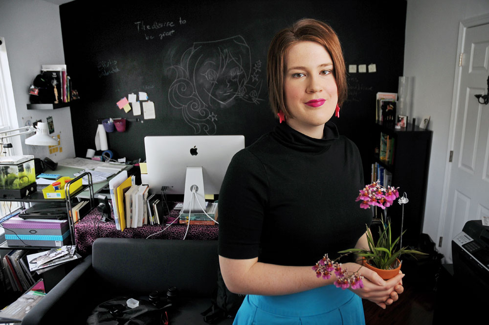 Rachel Nabors holds an orchid, standing in font of a pink leopard fur-covered desk. The wall behind is a chalkboard with cartoon drawings and post-its all over it.