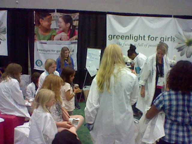 A gathering of women and girls at Greenlight for Girls's booth at OSCon.