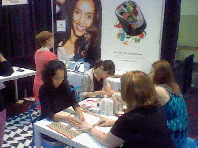 Logitech booth with women getting manicures