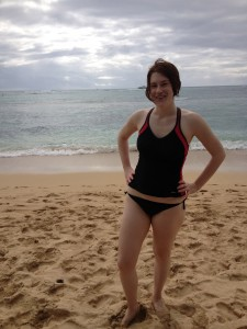 Rachel Nabors standing on a beautiful Waikiki beach in a tankini, the sun peeking out from clouds on the horizon.